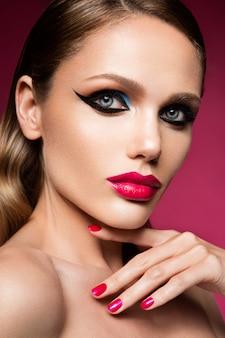Beau jeune visage féminin avec maquillage multicolore de mode lumineux