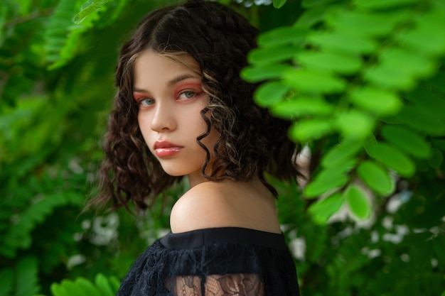 Beau jeune visage féminin soigné avec du maquillage près des feuilles vertes