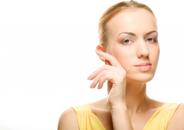 Beau jeune visage féminin avec un teint de bien-être - isolé
