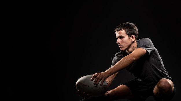 Beau joueur de rugby masculin athlétique tenant le ballon avec espace de copie