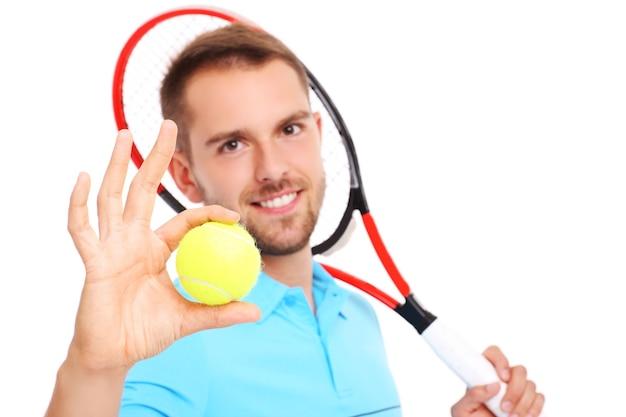Un beau joueur de tennis avec une raquette et une balle sur fond blanc