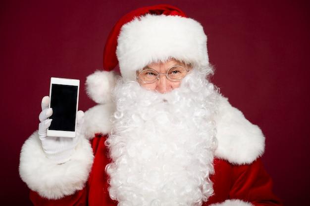Beau joyeux père noël montre l'écran blanc d'un smartphone