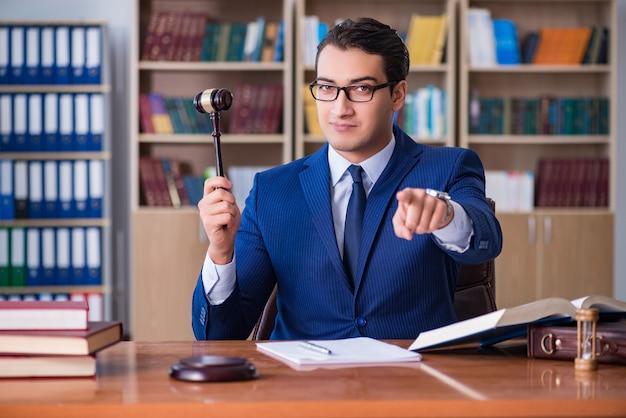 Beau juge avec marteau assis dans la salle d'audience