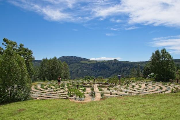 Beau labyrinthe de béton entouré de champs et d'arbres couverts d'herbe