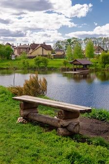 Beau lac calme avec un kiosque en bois dans un village de chalets ruraux. vacances à la campagne. week-end agréable dans la nature.