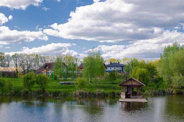 Beau lac calme avec un kiosque en bois dans un village de chalets ruraux. vacances à la campagne.