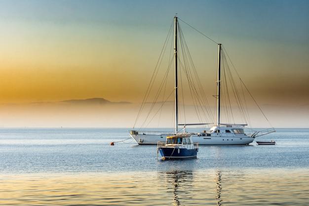 Beau lever de soleil sur la baie avec yacht