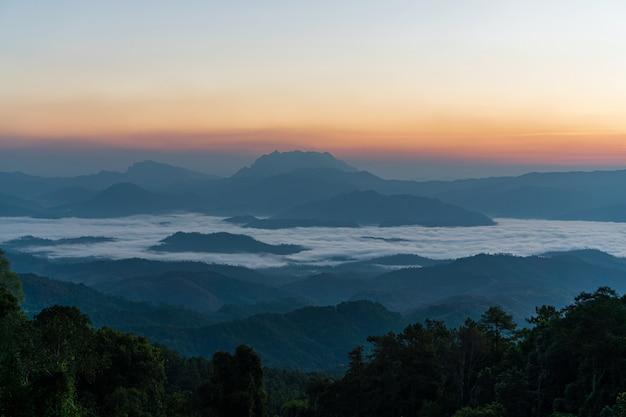 Beau lever de soleil et ciel coloré dans la brume sur la montagne