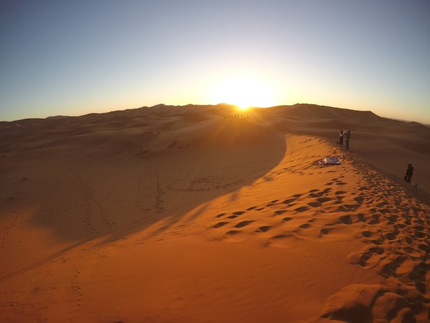 Beau lever de soleil dans le désert de merzouga dans les dunes de l'erg chebbi. maroc