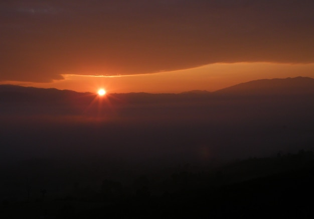 Beau lever de soleil sur une épaisse couche de nuages orange tendre