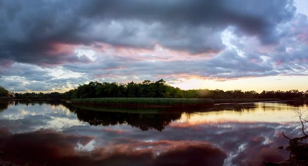 Beau lever de soleil avec des nuages lumineux reflétés dans le coucher du soleil des nuages du ciel du lac de l'eau