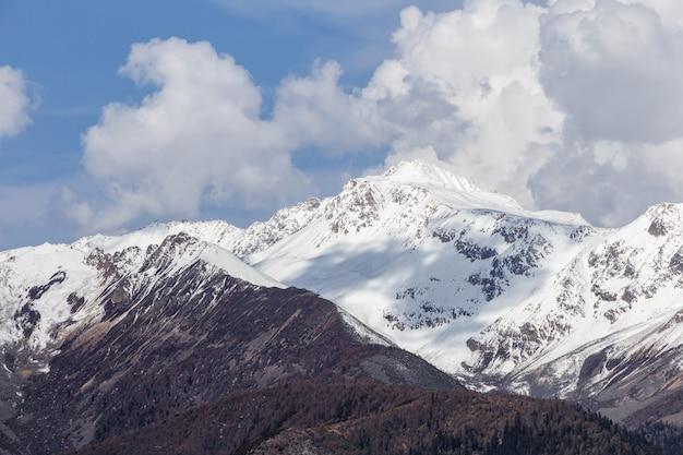 Beau lever de soleil nuageux dans les montagnes avec la crête de neige