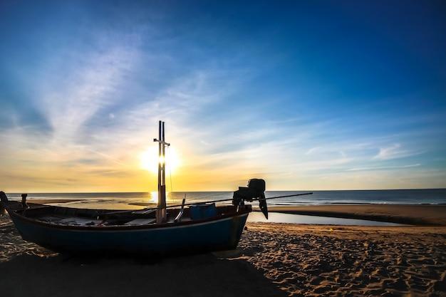 Beau lever de soleil sur la plage avec la silhouette du bateau