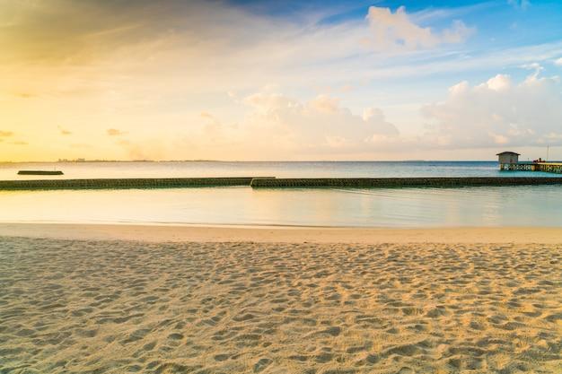 Beau lever de soleil sur la plage avec les villas sur l'eau dans l'île tropicale des maldives.