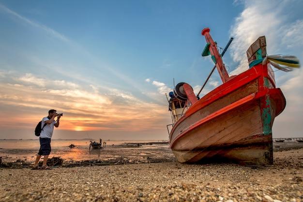 Beau lever de soleil sur un vieux bateau de pêche en bois sur la plage de thaïlande