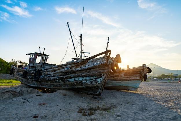Beau lever de soleil sur un vieux bateau de pêche en bois sur la plage