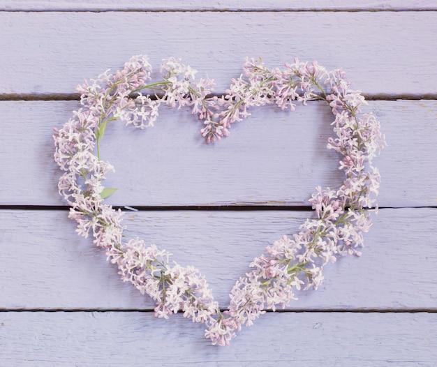 Le beau lilas en forme de coeur sur un fond en bois