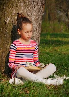 Un beau livre de lecture fille, assis dans le parc, sous l'arbre