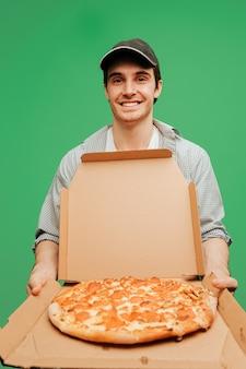Beau livreur de pizza ouvre la boîte avec pizza