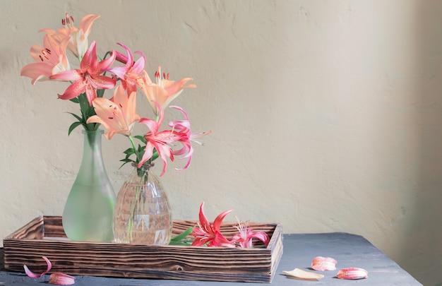 Beau lys dans un vase en verre sur une vieille étagère en bois