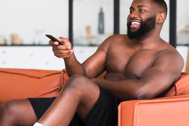Beau mâle adulte devant la télé