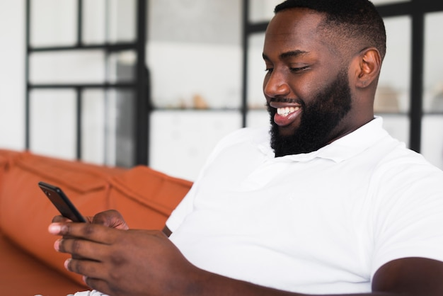 Beau mâle adulte parcourant son téléphone