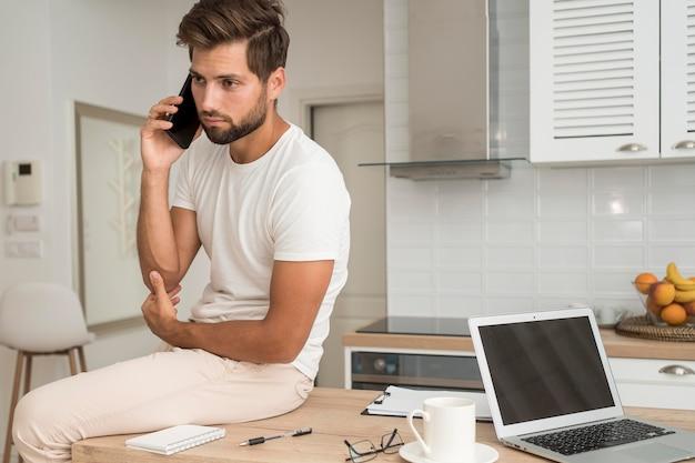 Beau mâle adulte parlant au téléphone