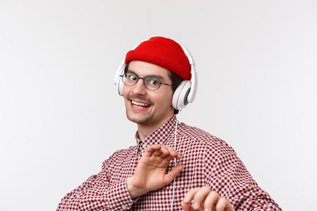 Beau mâle barbu sans soucis dans des verres et bonnet rouge dansant dans les écouteurs