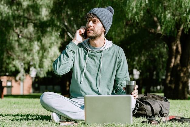 Un beau mâle avec bonnet appelant avec son téléphone portable tout en buvant un café. concept: la vie de nomade numérique