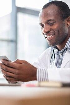 Beau mâle brune gardant le sourire sur le visage tout en se penchant les bras sur la table et en regardant le téléphone