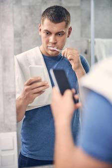 Beau mâle caucasien nettoyant ses dents devant le miroir tout en recherchant quelque chose dans le mobile