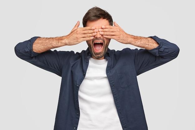 Beau mâle couvre les yeux des deux mains, garde la bouche largement, a du chaume, vêtu d'une chemise, attend la surprise, isolé sur un mur blanc. un jeune homme barbu regarde entre les doigts.