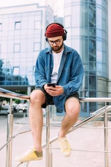 Beau mâle hipster barbu moderne regardant un cours en ligne sur smartphone dans des écouteurs sans fil. portrait vertical du corps entier.