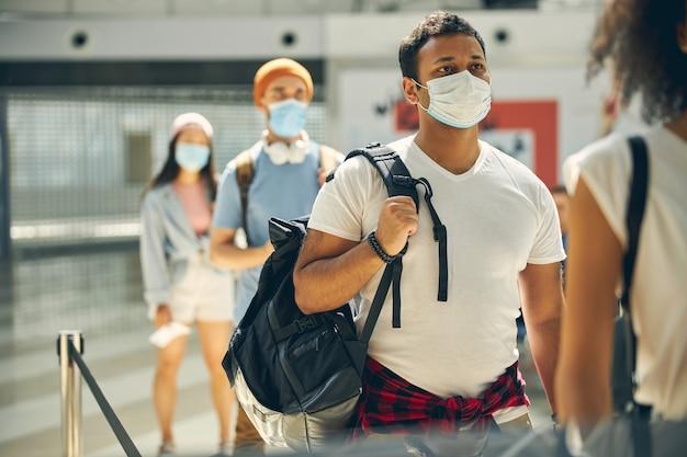 Beau mâle indien en chemise blanche tenant un sac à dos sur l'épaule en attendant un voyage en avion vers un autre pays