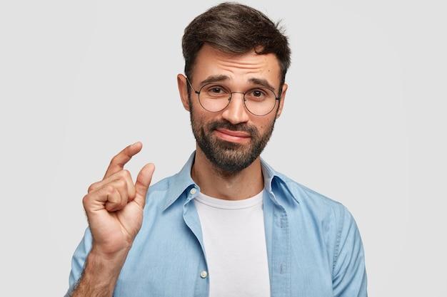 Beau mâle mal rasé avec des cheveux noirs et des poils épais, montre quelque chose de petit avec les mains, vêtu d'une chemise à la mode, isolé sur un mur blanc. jeune homme montre une petite chose à l'intérieur.