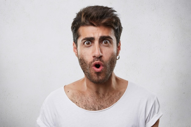 Beau mâle à la mode avec une barbe portant une boucle d'oreille et un t-shirt blanc à la recherche avec les yeux et la bouche largement ouverts exprimant sa surprise et son choc