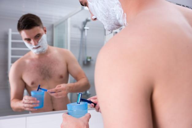 Un beau mâle avec de la mousse à raser sur les joues lave son rasoir dans la tasse avec de l'eau debout devant le miroir dans la salle de bain carrelée moderne à la maison