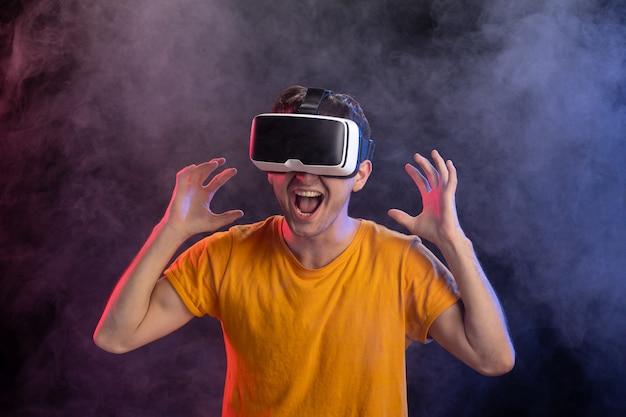 Beau mâle portant un casque de réalité virtuelle sur une surface sombre