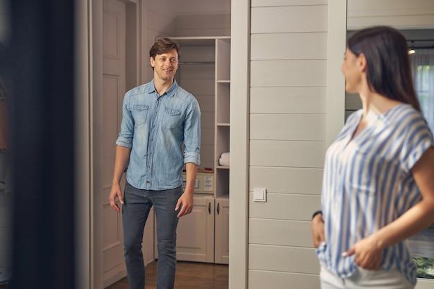 Beau mâle portant des vêtements décontractés en allant chez sa petite amie dans la pièce de couleur claire