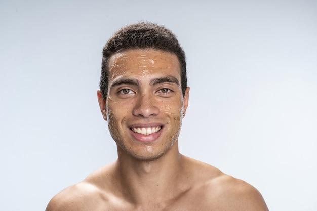 Beau mâle souriant portant un masque facial d'humidité