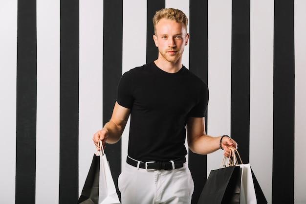 Beau mâle tenant des sacs à provisions