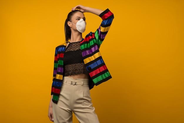 Beau mannequin fille mince posant dans un respirateur protecteur sur un espace jaune. veste couleur arc-en-ciel de la communauté lgbt