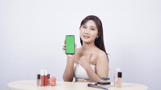 Beau maquillage asiatique montrant le geste ok de l'écran du smartphone isolé sur fond blanc