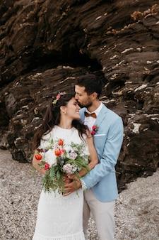 Beau mari et femme posant sur la plage à leur mariage