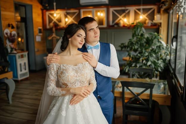 Beau mariage, mari et femme, mariée et le marié debout dans l'intérieur du loft près de la fenêtre. couple de jeunes mariés amoureux. le marié embrasse la mariée par les épaules. la mariée tient un bouquet de mariée dans les mains.