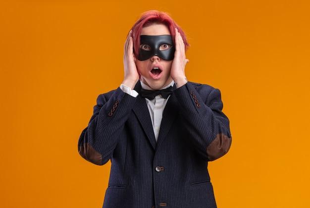 Beau marié en costume portant un nœud papillon et un masque de mascarade étonné et choqué avec les mains sur la tête debout sur le mur orange