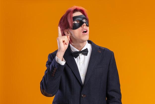 Beau marié en costume portant un nœud papillon et un masque de mascarade levant surpris en pointant avec l'index vers le haut