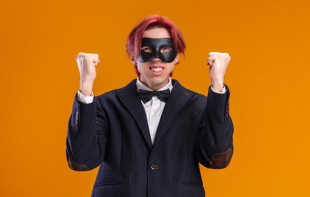 Beau marié en costume portant noeud papillon et masque de mascarade poings serrés heureux et excités debout sur le mur orange