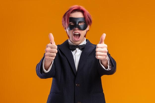 Beau marié en costume portant un nœud papillon et un masque de mascarade souriant joyeusement montrant les pouces vers le haut debout sur le mur orange