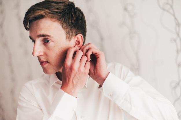 Beau marié élégant porte une boucle d'oreille à l'oreille sur fond blanc.